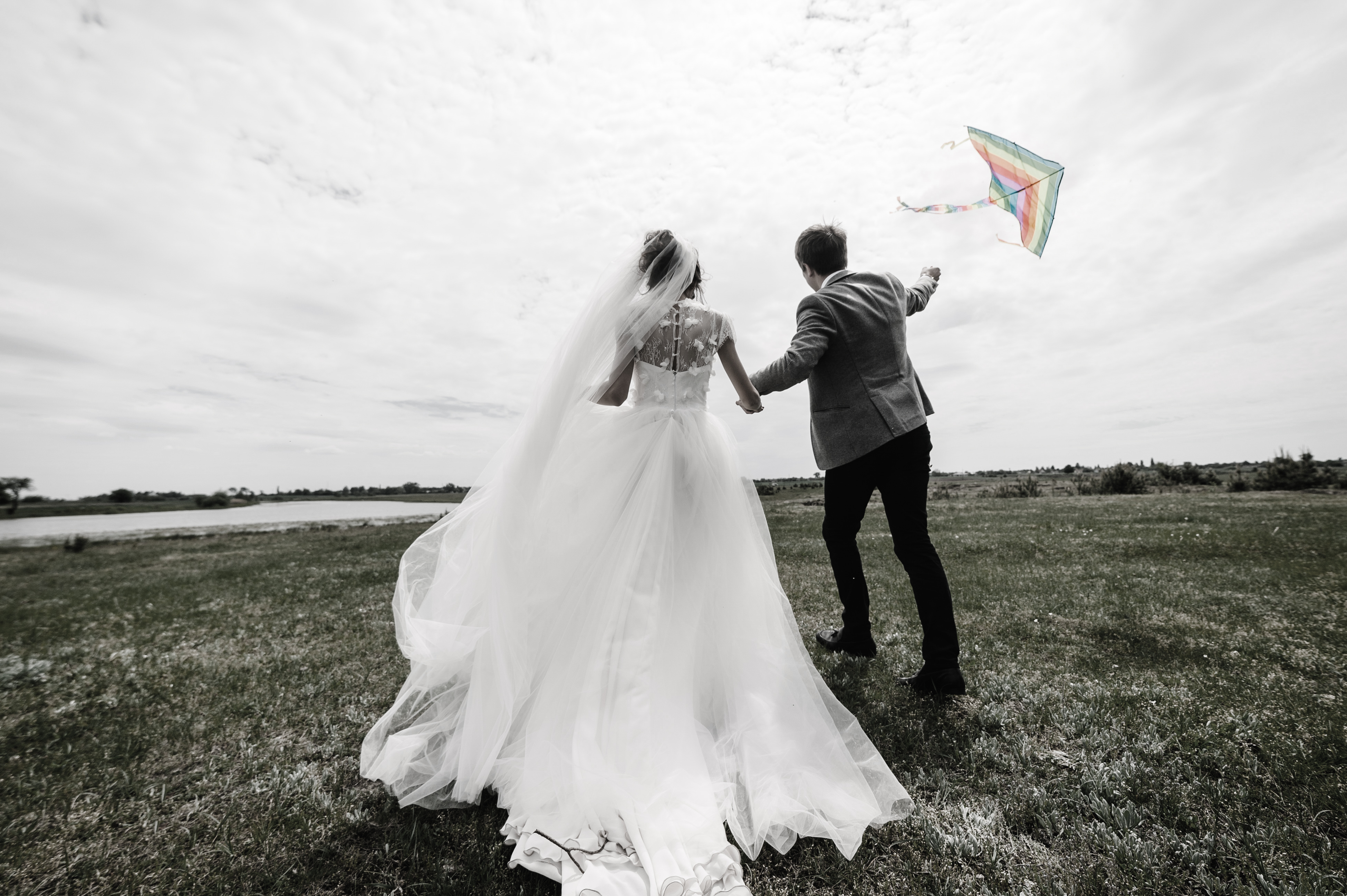 A wedding couple running back around the field letting kite fly and play and hold the kite. Bride and groom walk near lake in the nature flying a kite together on a wedding day.